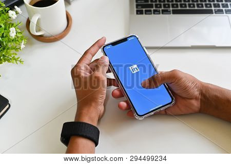 Chiangmai, Thailand - March 30, 2019: A Man Holds Apple Iphone Xs Max Open Linkedin Application On T