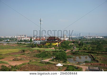 Chinese Village View With Yellow Temple And Big Antena Nearby, The Blury Look Of The City Buildings