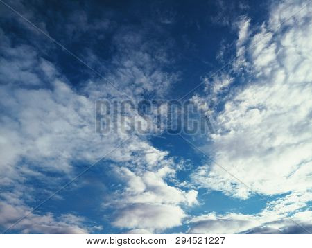 Blue sky background with white dramatic colorful clouds and sunlight. Colorful sky landscape, sky with picturesque clouds. Beautiful sky landscape view. Blue sky background with white clouds in the sky lit by sunlight