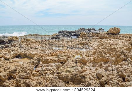 Beach Rocks, Rocks With Holes Made By The Waves Of The Sea. Spongy Rocks. Set Of Rocks Near The Sea