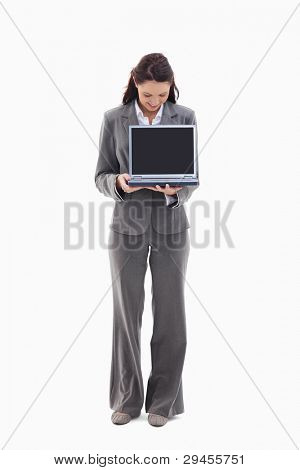 Businesswoman looking and showing a laptop screen against white background