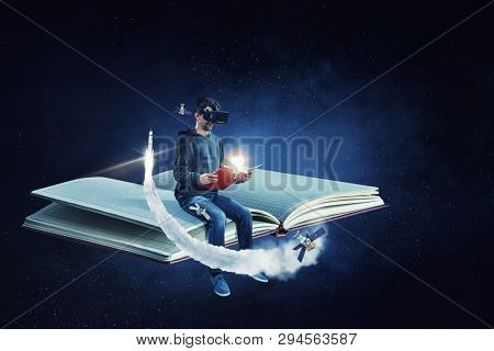 Virtual reality experience, young man in VR glasses. Mixed media