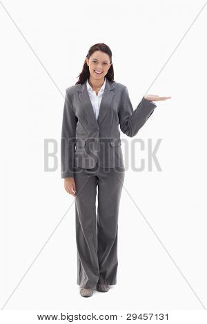 Businesswoman smiling and presenting a product against white background