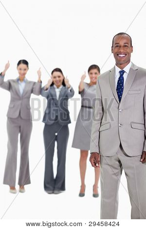 Happy businessman with three approving co-workers in background with thumbs up
