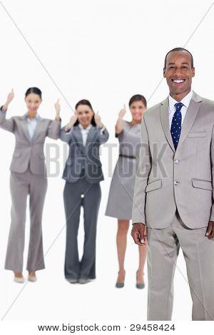 glücklich kaufmann mit drei Genehmigung co-Arbeiter im Hintergrund mit Daumen nach oben
