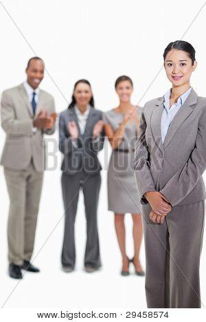 close up of a Businesswoman smiling with co-Arbeitnehmer applaudieren und Blick auf ihr im Hintergrund