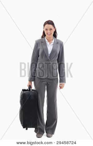 Businesswoman smiling with a suitcase against white background