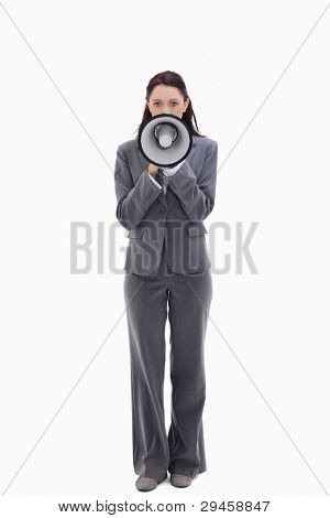 Businesswoman speaking in a megaphone against white background