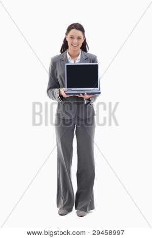 Businesswoman smiling while showing a laptop screen against white background