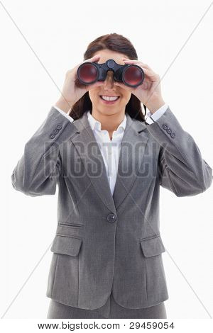Close-up of a smiling businesswoman looking through binoculars against white background