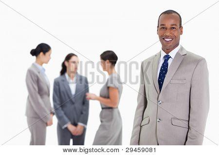 close up of a Businessman smiling mit drei weiblichen co-Arbeitnehmer ernsthaft reden im Hintergrund