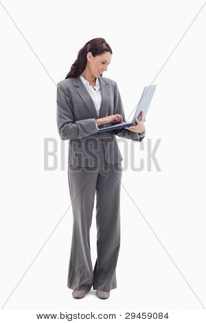 Businesswoman smiling while watching her laptop against white background