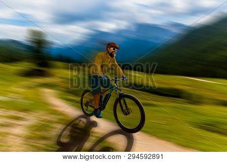 Single mountain bike rider on electric bike, e-mountainbike rides up mountain trail. Man riding on bike in Dolomites mountains landscape. Cycling e-mtb enduro trail track. Outdoor sport activity.