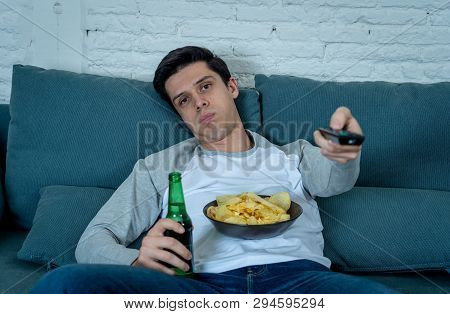 Close Up Of Bored Young Man Sitting On The Couch Watching Tv. Technology Overuse Concept