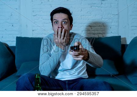 Picture Of Young Man Looking Scared Sitting On Sofa Watching Tv At Night. In Human Emotions Concept