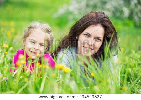 Mother and daughter lying on green summer grass with blooming yellow flowers