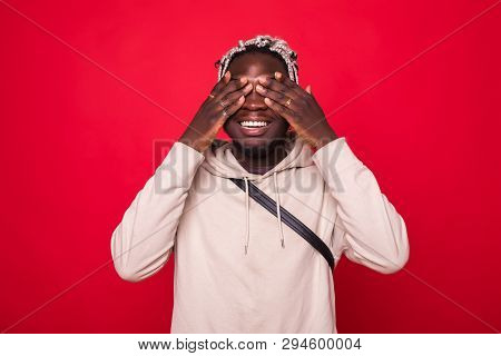 Closeup portrait, young male, shy man closing covering eyes with hands cant see, hiding, isolated red background. See no evil concept. Negative human emotion facial expression feeling reaction poster