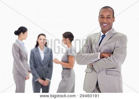 Close-up of a businessman smiling and crossing his arms with three female co-workers talking in the background