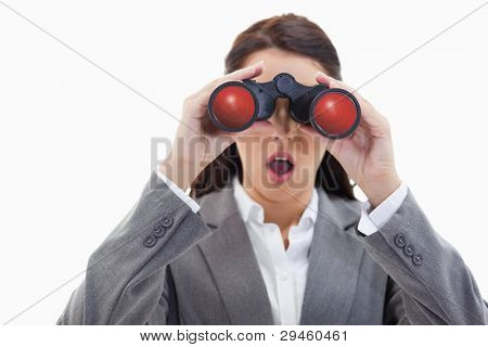 Close-up of a surprised businesswoman looking through binoculars against white background