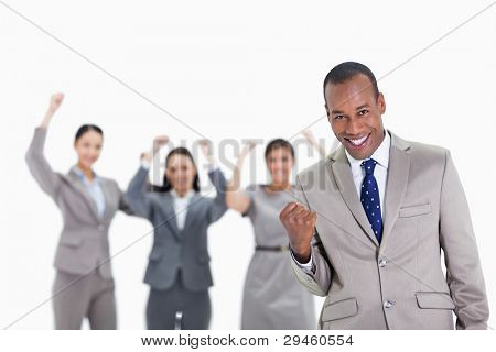 Close-up of a successful business team with man in foreground smiling and clenching his fist with three co-workers raising their arms