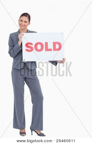 Happy real estate agent with sold sign against a white background