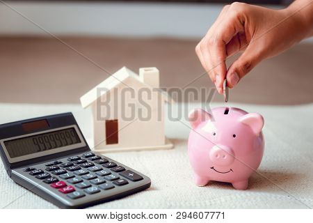 Close-up Woman Hand Is Putting A Money Coin Into Piggy Bank On The Bedroom., Female Hand Is Insertin