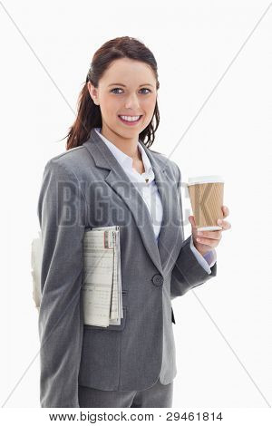 Close-up profile of a businesswoman smiling with a newspaper under her arm and holding a coffee against white background