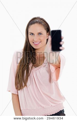 Close-up of a smiling girl showing a smartphone against white background