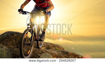 Cyclist in Red T-Shirt Riding the Bike in the Beautiful Mountains Down the Rock on the Sunrise Sky Background. Extreme Sport and Enduro Biking Concept.