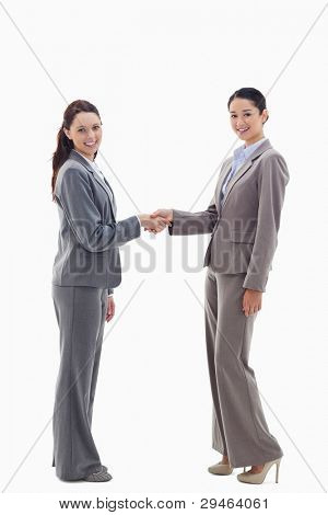 Two businesswomen shaking hands and smiling against white background