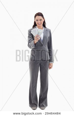 Businesswoman smiling and holding a lot of dollar bank notes against white background