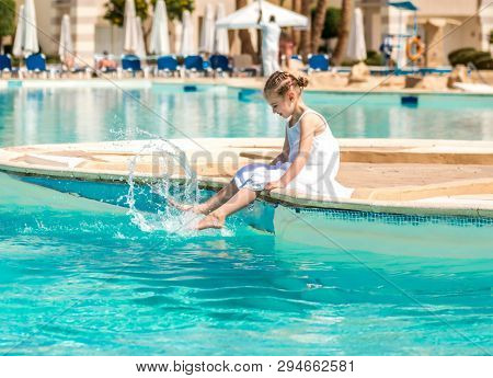 Active kid splashing in water by the pool side