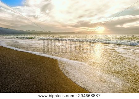 Ocean Sunset Is A Sandy Beach Shore At Sunset With A Gentle Wave Rolling To Shore