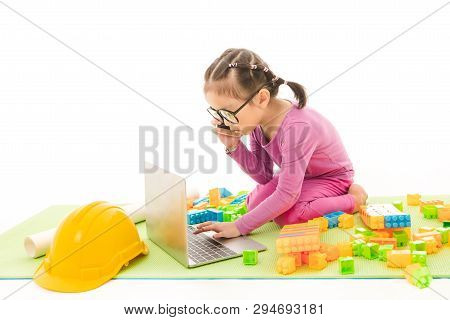 Cute Little Asian Girl Wearing Eyeglasses In Purple T-shirt And Pants, Role-playing Architect Busily