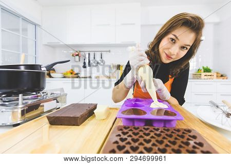 Beautiful Asian Female Cook In Orange Apron Using Pastry Bag Filling Hot Melt Chocolate Into Heart S