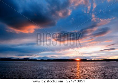 Sky sunset landscape - sea waters lit by sunset summer sky light. Summer sunny sky scene in picturesque tones. Sky summer nature with mountain range at the horizon of the sea