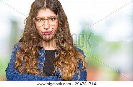 Young beautiful woman wearing glasses and denim jacket skeptic and nervous, disapproving expression on face with crossed arms. Negative person. poster