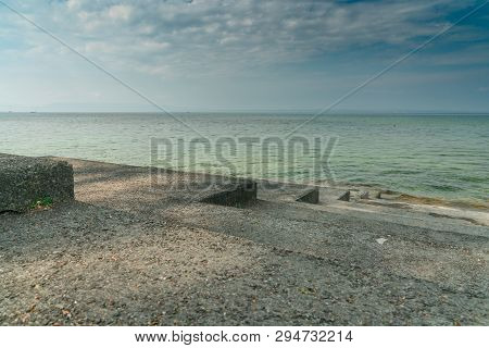 lakeshore on Lake Constance in Switzerland with an expansive view and concrete stairs leading into the water poster