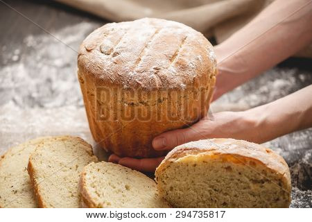 Hands Holding Homemade Natural Fresh Bread With A Golden Crust On An Old Wooden Background. Baking B