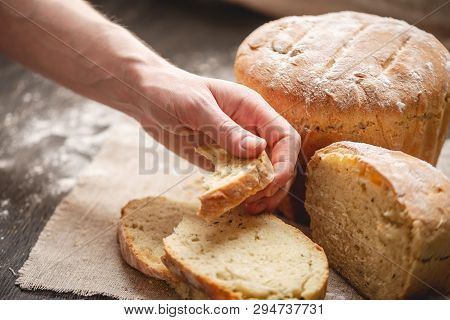 Hands Breaking Homemade Natural Fresh Bread With A Golden Crust On Old Wooden Background. Baking Bak