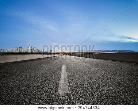empty highway road with seattle skyline background at night.