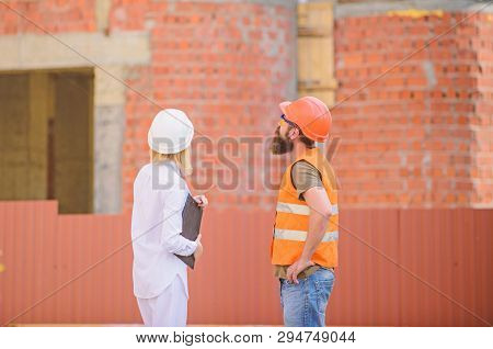 Construction Industry Concept. Woman Engineer And Bearded Brutal Builder Discuss Construction Progre