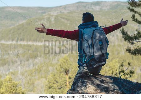 Man Hiker With A Large Backpack Stands On A Cliff Stone In Front Of A Green Valley With His Arms Out