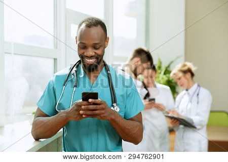Healthcare People Group. Professional African American Male Doctor With Phone Posing At Hospital Off