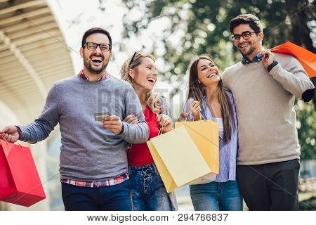 Friends Having Fun In Shopping Together, Holding Shopping Bags And Credit Card.
