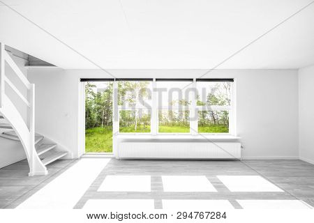 Bright Living Room With A View To A Green Garden In The Summer And Stairs On The Left