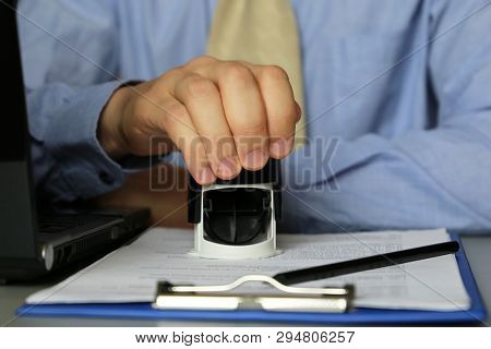 Man In Business Clothes Puts A Stamp On The Documents In The Office. Concept Of Official, Custom Off