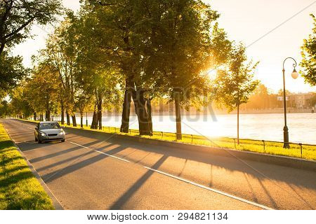Front View Of Modern Car Driving Or Traveling At Asphalt Road In The Park At Beautiful Sunset, Stree