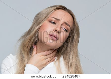 Closeup Portrait Of Attractive Upset Young Blonde Woman In White Top Having Sore Throat, Holding Han