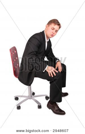 Young Man In Suit Sits On Chair